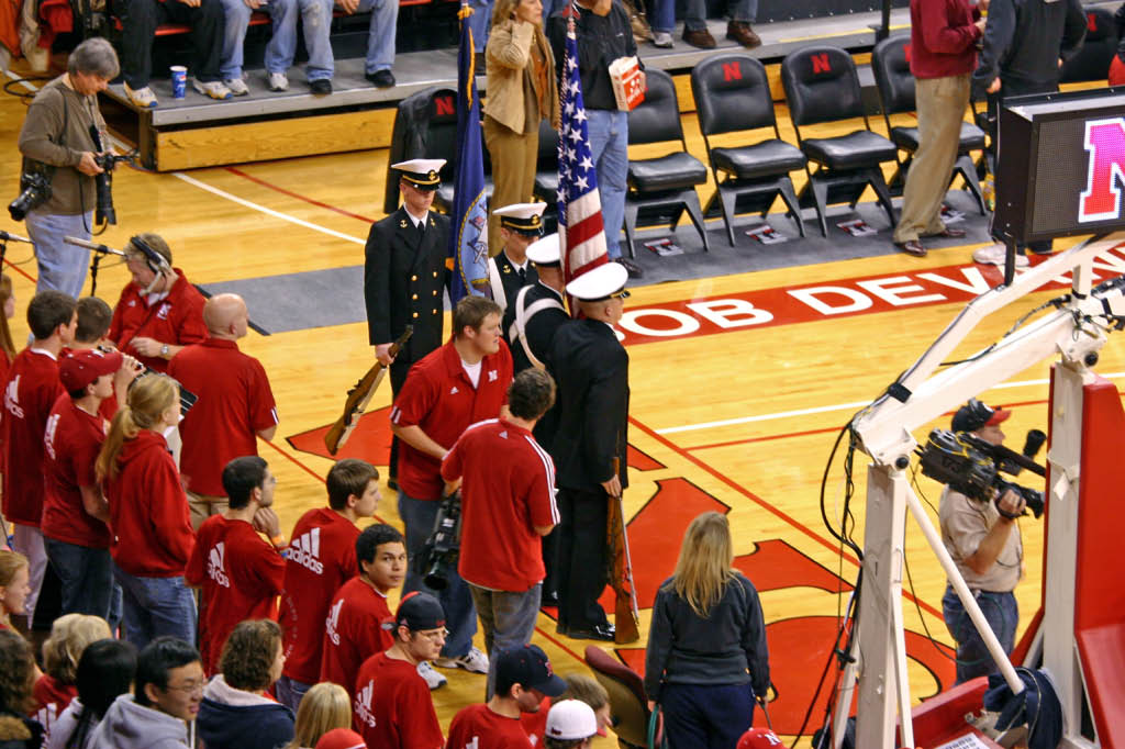 Quietly, the Navy ROTC Color Guard appeared on the sideline.